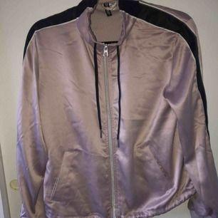 En pastell lila jacka från H&M. Har snören borde i halsen och längst ner. Har dragkedja.  Frakt ingår inte