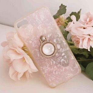 Urvackert halvgenomskinligt rosa mobilskal till iPhone 6(S), 7 samt 8 🌸 I mitten är en guldring omringat av små diamanter med stor vit pärla som dessutom går att fälla ut - asbra när man typ ska kolla på film!! Jag bjuder på frakten 💌