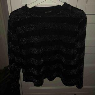 Stickad tröja med svart o silverglittriga ränder. Samt mindre slita på sidorna, från h&m. Använd ett par gånger men bra skick. Skulle säga att den passar bäst om man har M-L blir lite stor annars. Frakt 50, pris kan diskuteras.