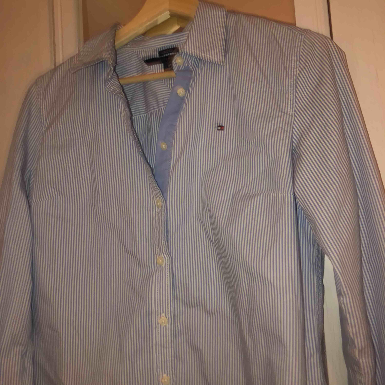 Jätte snygg och stilren blå-vit randig skjorta från Tommy Hilfiger! Jätte snygg bara sådär med jeans eller så kan man också styla med en stickad tröja över! Ttyvärr växt ur den men den är sparsamt använd✌🏼. Skjortor.