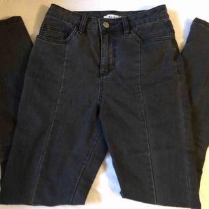 Gråa jeans från NA-KD storlek 34! Söm längs hela byxan ner och en slits på vardera ben där fram. Använda kanske 3-4 gånger 🦋  Finns att hämta i Göteborg, annars står köparen för frakten (ca 50 kr).