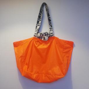 Ann-Sofie Back neon orange logo tote, haft den i flera år och väl använd men i bra kvalité, handtaget har dock blivit lite nopprigt av att fastna i kardborren. Några svaga mindre fläckar finns också, har bara handtvättat den och inte testat med fläckborttagare eller tvättmaskin. Säljs därför billigt, dyr i inköpspris! Frakt 59 kr.