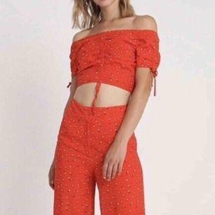 Rött blommigt set med byxor och singoalla-topp ifrån Elsa Hosks kollektion med BikBok. Både byxorna och toppen är helt oanvända med prislappen kvar.  Finns för avhämtning i Lund. Kan även skicka, tror det kostar max 75kr!