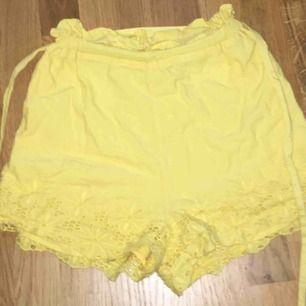 """gul fina shorts som är köpta på bikbok men jag tycker dem var lite för gula för min smak, man får till ett band som man knyter i midjan. spets på kanten av shortsen o på ändarna på """"skärpet"""""""