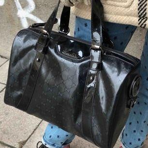 Klassisk svart Gucci väska i Guccis GG monogram. Färg: Black. Material: Imprime Leather. Mått: Höjd: 28 cm. Bredd: 30 cm. Djup: 18 cm. Handtag: 30 cm, ca 12 cm upp till handen.Finns att hämta på Södermalm. Vid leverans tillkommer frakt!