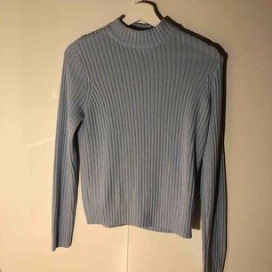 Stickad ljusblå tröja med liten polokrage