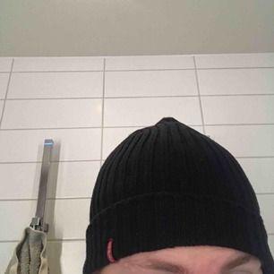 Skitsnygg svart stickad mössa mössa från Levi's. Man kan vika upp och ner nedersta kanten och märket syns och är rätt ändå