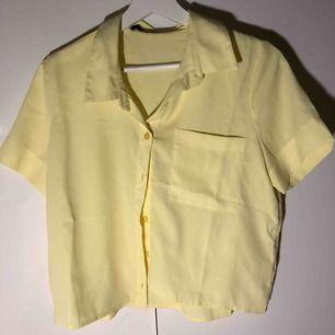 Gul kortärmad skjortblus med ficka på bröstet på ena sidan