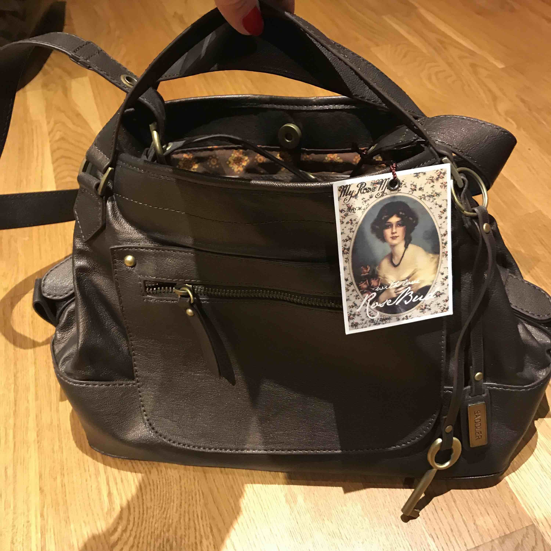 Helt ny Saddlerväska- Rosenud. I brunmetallic.  Köparen står för frakt . Väskor.