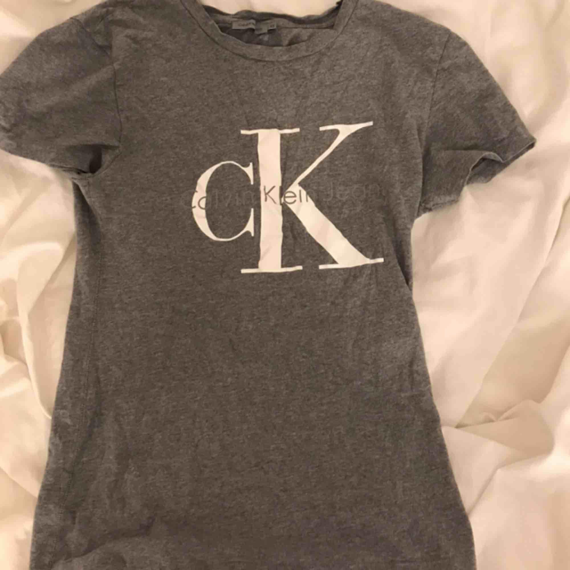 Grå T-shirt från Calvin Klein. T-shirts.