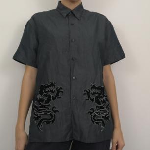 Skitsnygg skjorta med två sammetsdrakar på framsidan. Den gråa färgen på tyget är nästan glansig/skimrig i vissa ljus. Super y2k! Frakten för denna ligger på 36 kr, samfraktar gärna! 😌👍