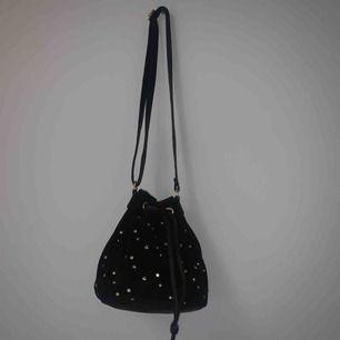 Mindre väska som passar sååå snyggt att bara slänga över armen! Aldrig använd!! Den är i fuskmocka med snygga fuskpärl detaljer😍 Väskans axelband är även justerbart! Köparen står för frakt!