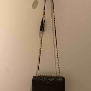 Crossbodybag från Tory Burch. Svart med gulddetaljer. Mycket fint skick såväl utvändigt och inuti.