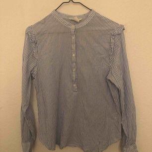 Söt randig blus i materialet som en skjorta. Vit och blå randig. Passar även om man har storlek 36.