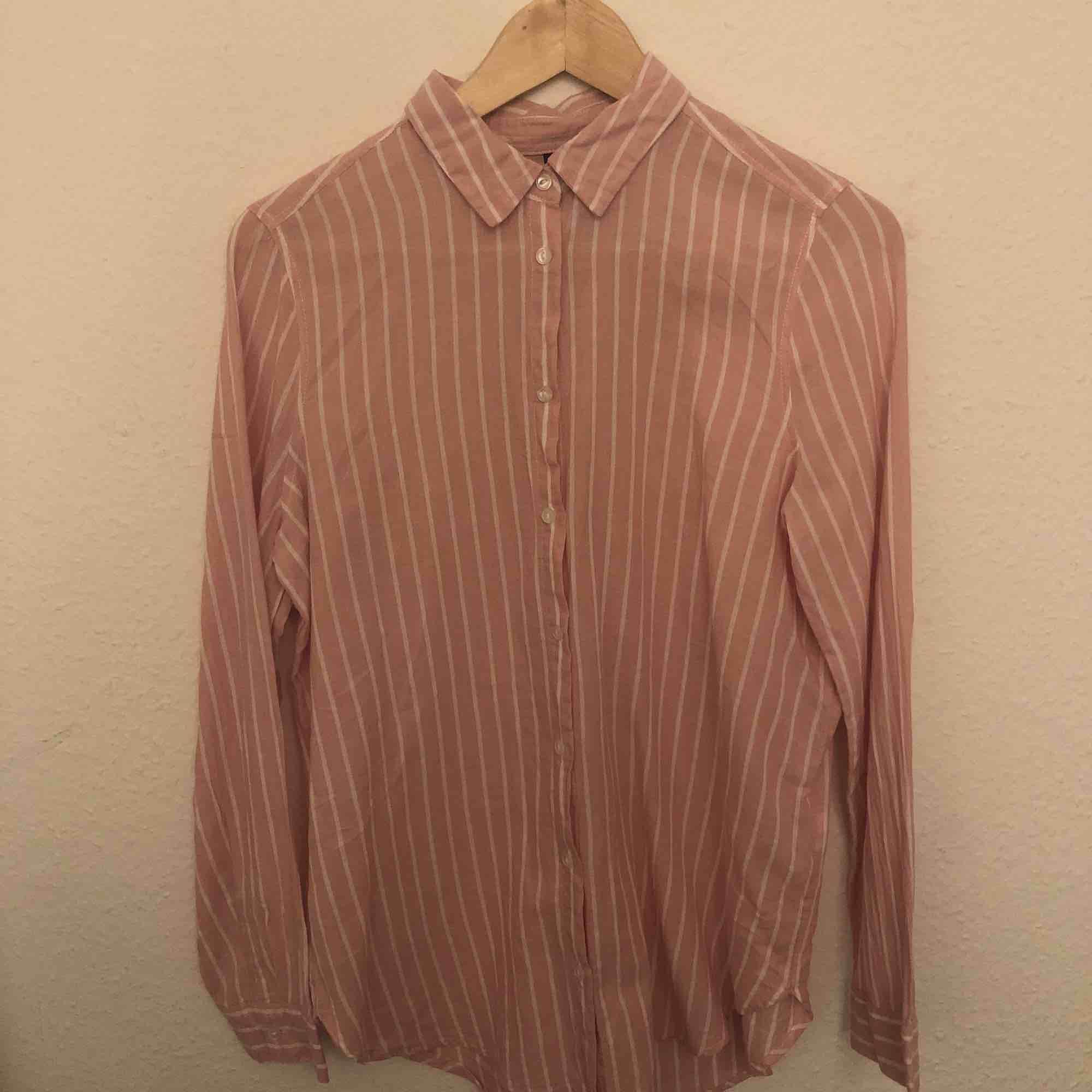Randig skjorta av lite tunnare material och lite längre modell. Rosa och vit randig. . Skjortor.