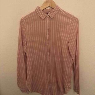 Randig skjorta av lite tunnare material och lite längre modell. Rosa och vit randig.