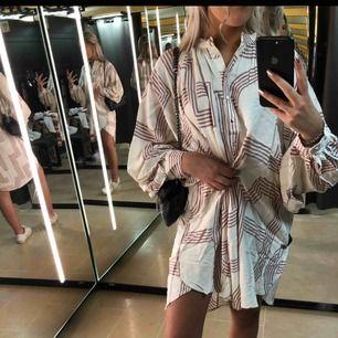 Lite oversized klänning i nyskick, superfin att ha med ett skärp i midjan :) Klänningen är vit med vinröda inslag som ni ser på bilden. Skriv om ni vill ha fler speciella bilder på den