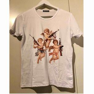 Söt vit t-shirt med änglar på! Änglarna håller i AK47or🤩 Väldigt tuff och otroligt bekväm! Passar XS-M, men markerade storleken är M. Frakt tillkommer💞