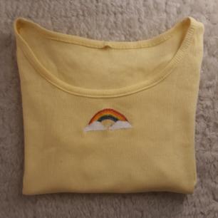 Ljus gul t-shirt med korta ärmar och en målad regnbåge. Den är lite genomskinlig därav priset. Fråga om du har nån eller  vill ha mer bilder😋🌈  Tvättas i 40°C