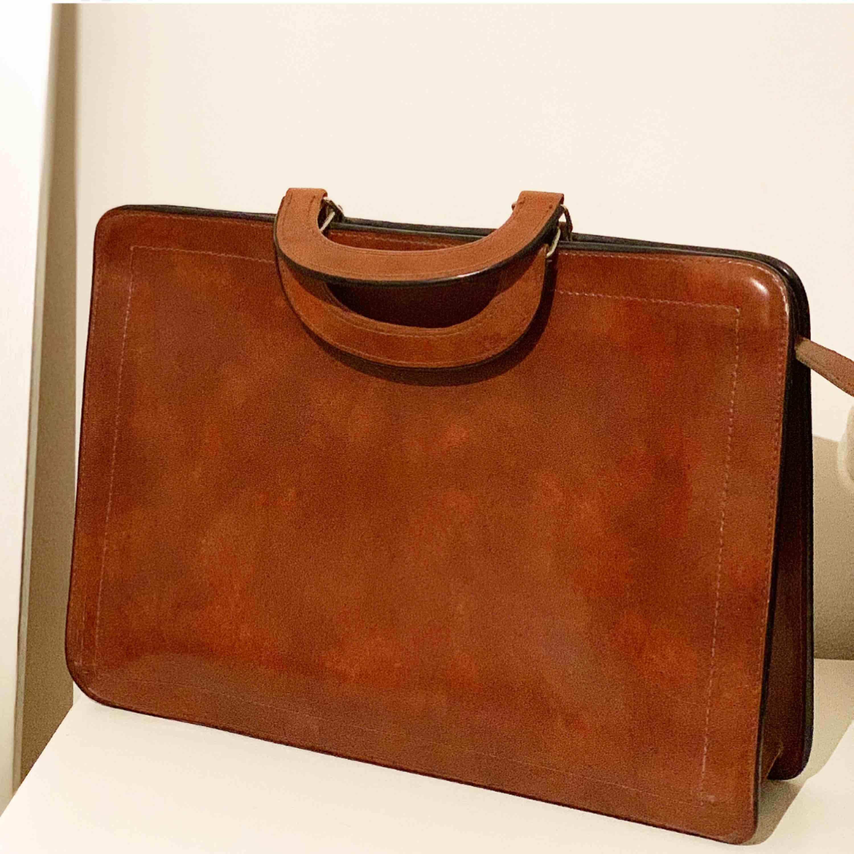 Snygg väska perfekt för dator i brun skinn imitation. Köpt på secondhand. . Väskor.