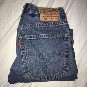 Levis 501 i gråaktig blå färg med två hål vid knäna. På jeansen står det storlek 38/32 men den är i verkligheten för 27/32. Antar därför att vintagebutiken jag köpte i har förminskat jeansen.