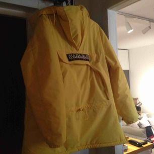 En napaijir jacka gul är mycket varm och skön i minus grader , fryser inte i den , har en öppning på sida. Och en luva samt en fixa i mitten av jackan köpt för ett år sedan är i mycket bra skick nypris 3100kr