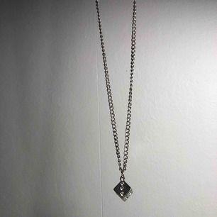 Halsband med en tärning på i bra skick, köparen betalar frakten!