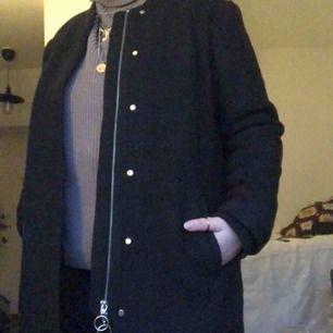 Svårt/grå kappa i tjockare material, ganska varm. Har både dragkedja och knappar