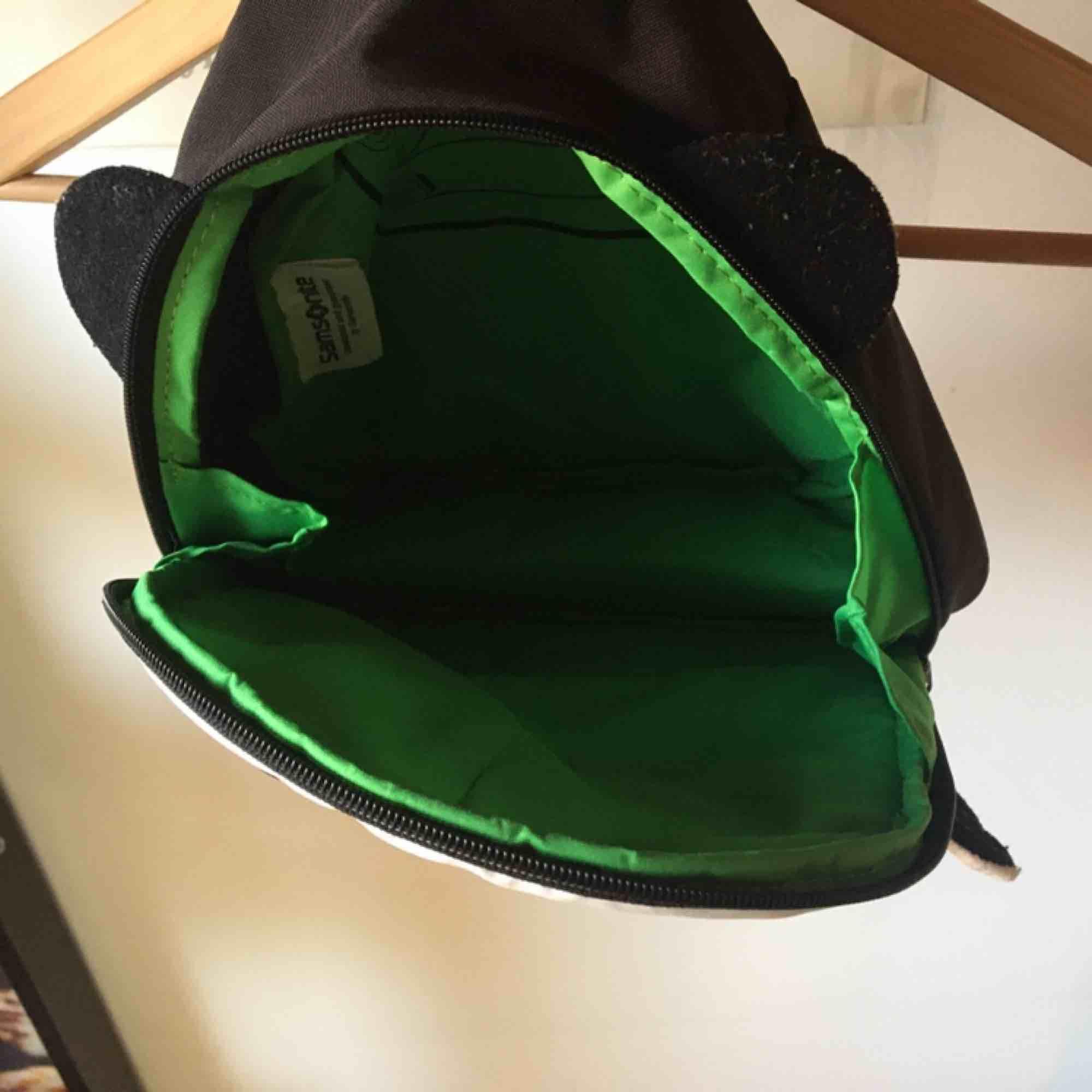 Söt pandaryggsäck med grönt foder på insidan. Nopprorna på örat tas bort med maskin innan försäljning såklart. Knappt använd och i fint skick. Vid frakt står köparen för kostnaden 🐼. Väskor.