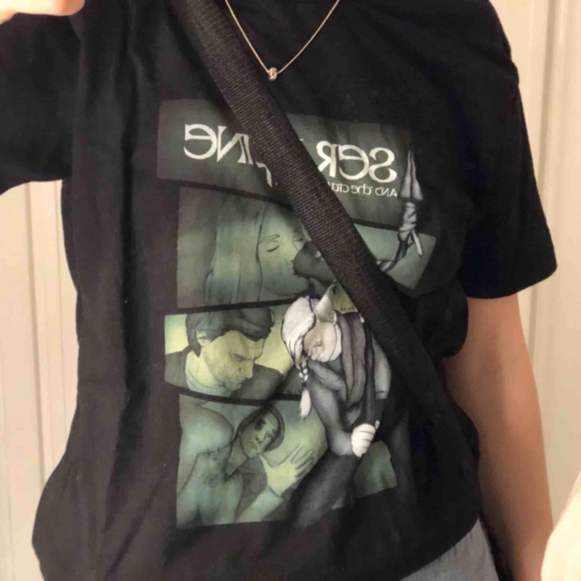En svart t-shirt med grönt tryck. Köpt på secondhand  men säljer pga att den kommer inte till användning. Jätte fin och i okej skick🥰. T-shirts.