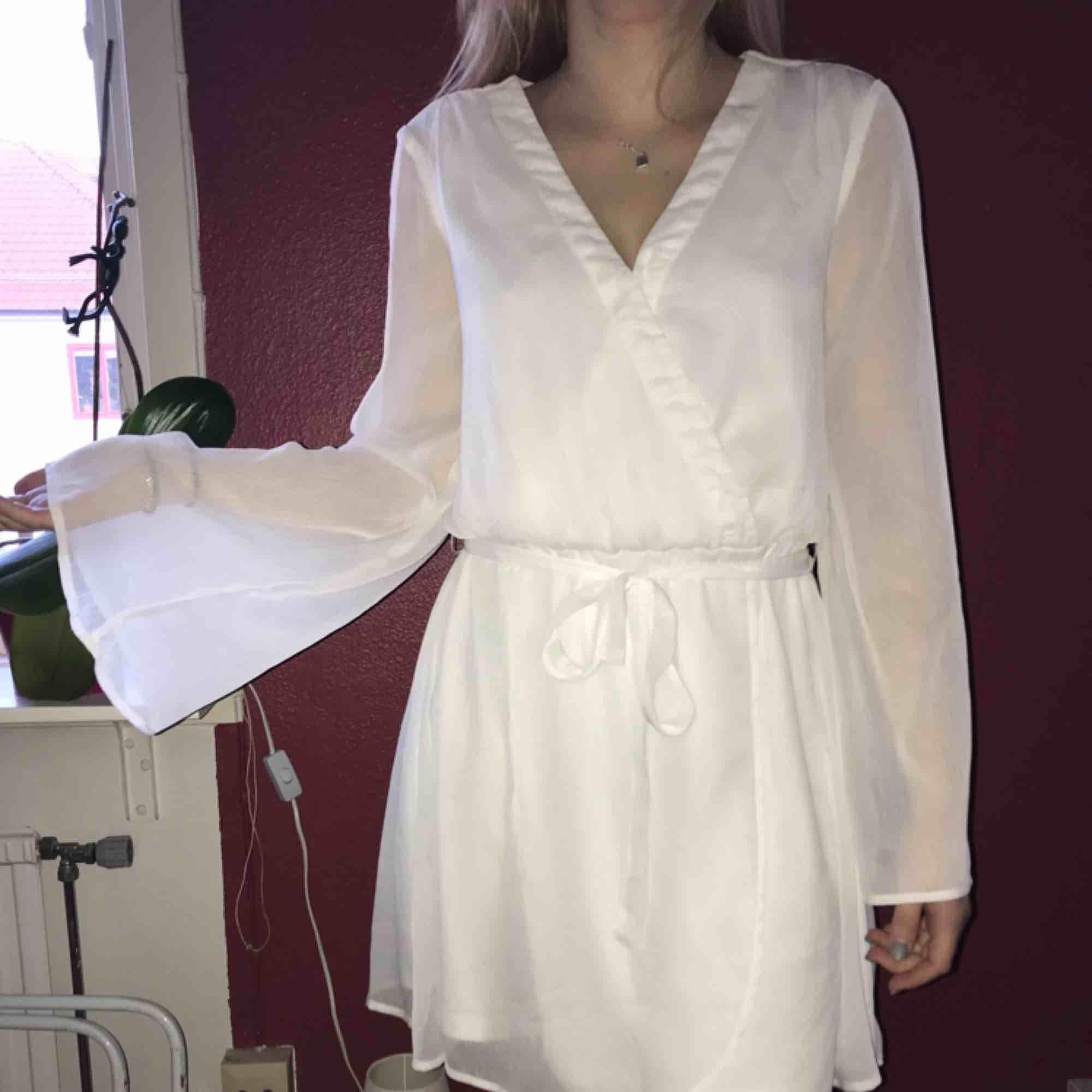Vit klänning från Nelly.com. Aldrig använd. Rätt tunn och vida armar (se bild).Storlek 34 men är rätt stor passar även 36/38. Frakt mot kostnad :). Klänningar.