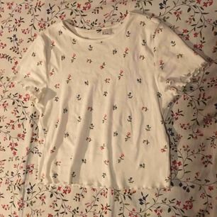 Söt vit tröja med blommor och söt form på ärmsluten och i slutet av tröjan. Sparsamt använd och i mycket fint skick. Vid frakt står köparen för kostnaden 👼🏻