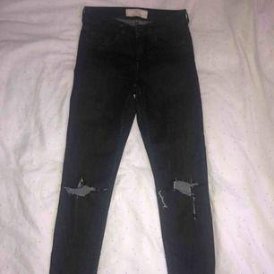 Svarta jeans med slitningar på knäna. Helt ok skick med en liten fläck som syns på tredje bilden, inte helt säker på om den försvinner därav priset.