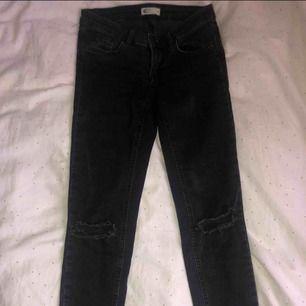 Svarta lågmidjade jeans med slitningar från Gina tricot. Bra skick.
