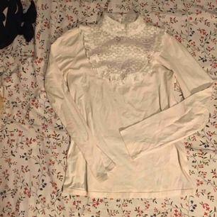 Fin vit tröja med polokrage och fina spetsdetaljer. Den har en sminkfläck vid armen som jag inte fått bort men går kanske med rätt medel. Ena galgen i halsen är trasig men påverkar inte tröjan alls. Övrigt fint skick! 👼🏻