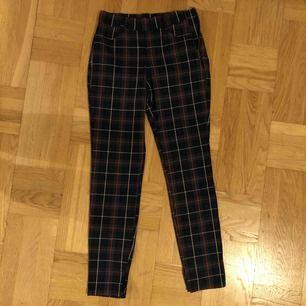 Rutiga byxor från Zara i färgerna grön/blå/rött. Tight modell med liten slits i slutet av byxbenet. Dragkedja på sidan av höften. Aldrig använda. Fraktkostnad tillkommer.