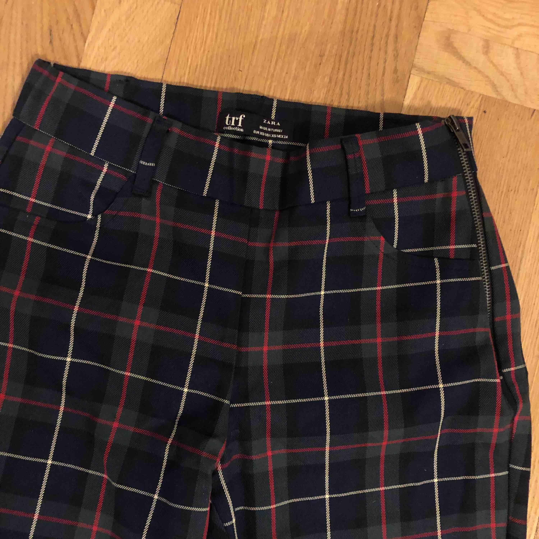 Rutiga byxor från Zara i färgerna grön/blå/rött. Tight modell med liten slits i slutet av byxbenet. Dragkedja på sidan av höften. Aldrig använda. Fraktkostnad tillkommer.. Jeans & Byxor.