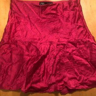 Rosa kort kjol från Zara. Glansigt fejksiden och lite skrynklig i utseendet.