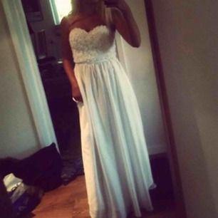 Säljer min vackra vita långa balklänning mjuk som silke och som är använd endast en gång! Det är storlek 36 och den har ett blommönster lite likt spets upptill. Jättefint skick. Originalpris: 799 kr