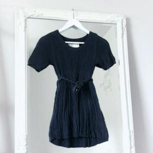 Färg: mörkblå/navy.  Strl: 12= XS.   Snygg stickad tunika med tillhörande knytband med öglor i midjan, avtagbart. Halvlång. Fraktkostnad tillkommer, betalning via swish.