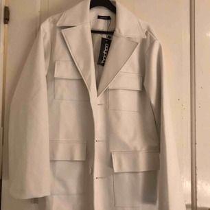 En fin vit fake skinn jacka från bohoo helt ny ingår ett skärp till jackan köparen står för frakt vid eventuell leverans (postas)