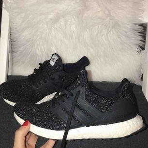 """Ett par Adidas ultra boost, svart. Skon har även  lite vita """"prickar"""". Dom är använda en enda gång, därav de höga priset. Priset kan diskuteras. Ordinarie pris 1 799:-"""