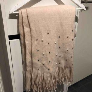 Den här mysiga halsduken är nu till salu eftersom den inte kommer till användning!  Den är mjuk och väldigt stor, ca 60 cm x 120 cm och har fina pärlor i olika färger längst med båda ändar.   Endast använd ett fåtal gånger så är som ny!