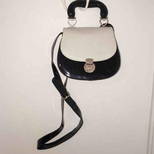 Supersöt vintage-inspirerad väska från Topshop med tillhörande axelrem. Detaljer i metallen som är formade som hjärtan, i god skick men har en repa på baksidan, inget som syns dock när man använder den.