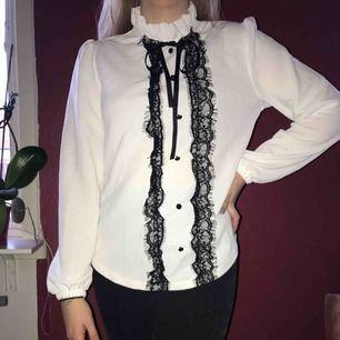 Vit tröja med svarta detaljer i spets bland annat. Helt ny och oanvänd. Storlek S. Frakt mot kostnad