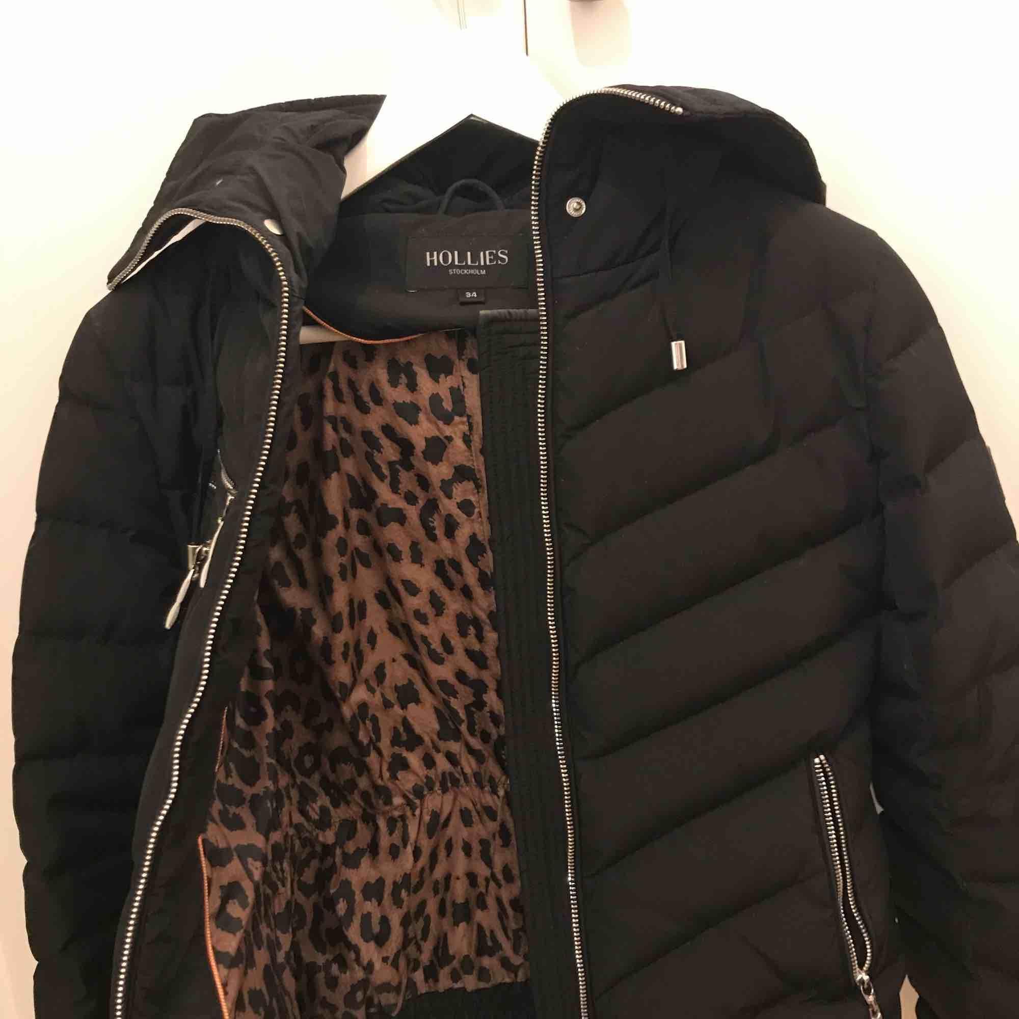 Jättefin och varm svart vinterjacka med leopardmönster inuti med pälsluva från Hollies! Använd ett par fåtal gånger så väldigt bra skick. Kostade 3500, säljer för 1000kr (frakt ingår). Jackor.