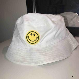 Fiskehatt med gul smileys. Aldrig använd