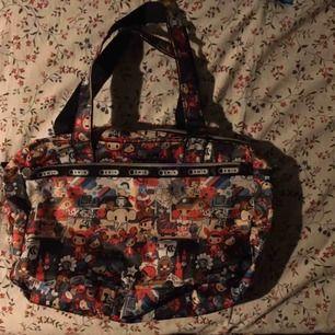 Väska med massor av söta figurer på! Aldrig använd och därför i nyskick. Axelrem medföljer (helsvart) och den är mjuk i tyget och går att packa rätt rejält. Vid frakt står köparen för kostnaden 👼🏻