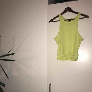 Ribbat brottarlinne i neongulgrön färg. Storlek L men stretchigt material. Lite kortare modell.