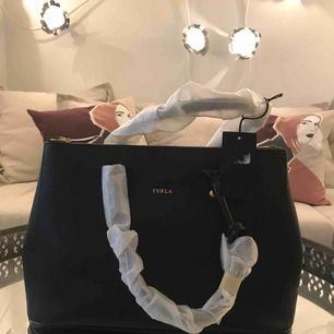 En svart väska ifrån äkta Furla Dust bag och prislapp tillkommer! Kvitto finns ej kvar. Aldrig använd och handtagen är fortfarande inpackade.  Vid flera intressen, budgivning!